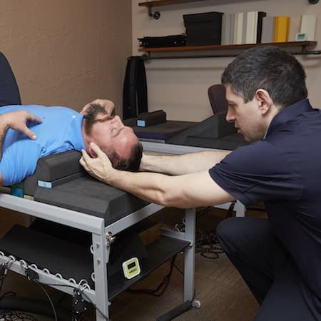 Dr. Fish adjusting the spine of a patient who is on their side. He is using a flexion table for back pain at Genesis Chiropractic Clinic in Horsham PA 19044
