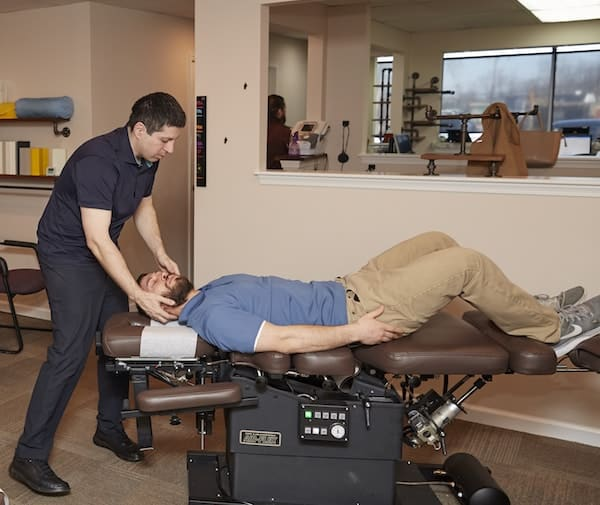 Dr. Gene Fish adjusting the neck of a male patient who has been experiencing chronic neck pain