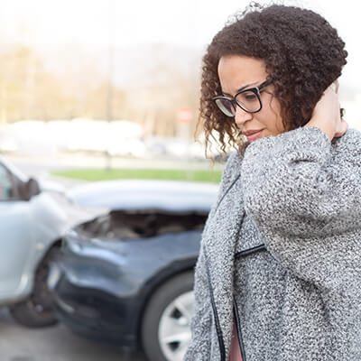 Woman holding the top of her back with a smashed car in the background