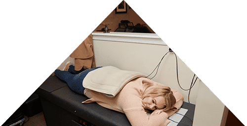 A woman laying on a rehab table with a heat pack on her back to help circulation.